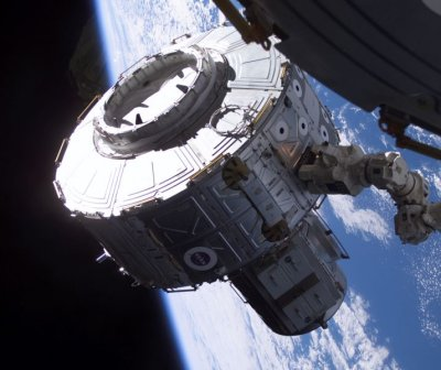 The International Space Station's robot arm, operated by Expedition 2 Flight Engineer Susan Helms, moves the Joint Airlock into position