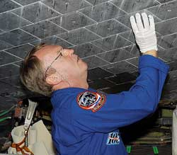 Astronaut Andy Thomas takes a close look at a Space Shuttle tile. Credit: NASA