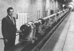 Light-gas gun. Thomas N. Canning holds model that is fired down range. Plastic pistons are seen stacked against wall at left. Credit: NASA