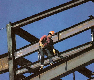 A steel worker balances on the framework of a building for the Los Angeles County Museum of Natural History