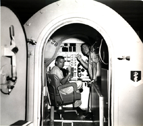 Air Force personnel performing experiments in the Two-Man Simulator at the School of Aerospace Medicine, circa 1965