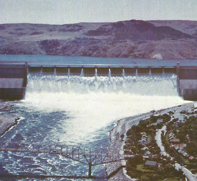 A dam holds water at a height and when the water is released its potential energy changes to kinetic energy that can be converted into useful electrical energy by water turbine generators,